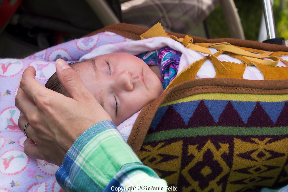 Seattle, Washington: May 26, 2014: The Native community put on a mini Pow Wow during the annual Folklife festival at Seattle Center. There a baby in attendance sleeps, swaddled in a papoose.