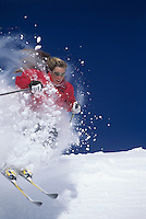 Skier skiing through powdery snow on ski Slope