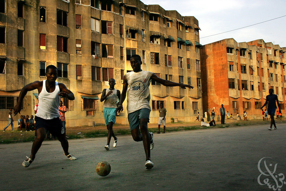 "Ivorian men wearing plastic shoes called ""korodjo"" play a game of street football in a poor district of the Port Bouet neighborhood of Abidjan, Côte d'Ivoire February 17,2006. Football is an integral part of the social fabric that makes up Ivorian society."