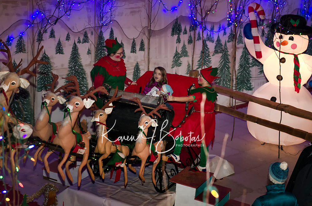 Miley Hingston rings the bells as she takes off for the North Pole in Santa's sleigh with the help of elves Hot Cocoa and Egg Nog during opening night of Christmas Village.  (Karen Bobotas/for the Laconia Daily Sun)