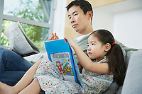 Daughter with picture book sitting beside father on sofa with newspaper side view