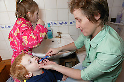 Single parent helping her young son clean his teeth,