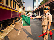 20 MARCH 2015 - BANGKOK, THAILAND:   A State Railways of Thailand worker waves a 3rd class train coming into Bangkok through the Khlong Tan train station in a residential section of Bangkok. The State Railways of Thailand (SRT), established in 1890, operates 4,043 kilometers of meter gauge track that reaches most parts of Thailand. Much of the track and many of the trains are poorly maintained and trains frequently run late. Accidents and mishaps are also commonplace. Successive governments, including the current military government, have promised to upgrade rail services. The military government has signed contracts with China to upgrade rail lines and bring high speed rail to Thailand. Japan has also expressed an interest in working on the Thai train system. Third class train travel is very inexpensive. Many lines are free for Thai citizens and even lines that aren't free are only a few Baht. Many third class tickets are under the equivalent of a dollar. Third class cars are not air-conditioned.    PHOTO BY JACK KURTZ