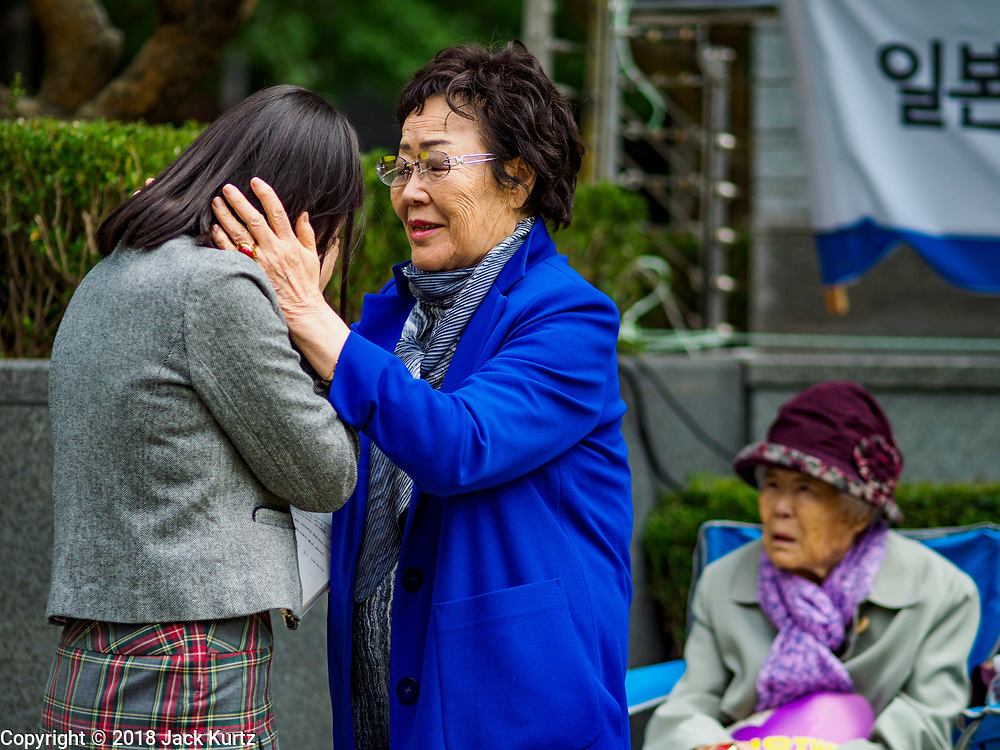"10 OCTOBER 2018 - SEOUL, SOUTH KOREA: LEE YONG-SOO, one of the few surviving ""comfort women"" comforts a South Korean student who spoke during the Wednesday Demonstration to protest Japan's sexual enslavement of Korean women during World War II. Lee has said she was tortured with electic shock and raped by Japanese soldiers four to five times a day during her enslavement. The Wednesday protests have been taking place since January 1992. Protesters want the Japanese government to apologize for the forced sexual enslavement of up to 400,000 Asian women during World War II. The women, euphemistically called ""Comfort Women"" were drawn from territories Japan conquered during the war and many came from Korea, which was a Japanese colony in the years before and during the war. The ""comfort women"" issue is still a source of anger of many people in northeast Asian areas like South Korea, Manchuria and some parts of China.        PHOTO BY JACK KURTZ   <br /> Wednesday Demonstration demanding Japan to redress the Comfort Women problems"