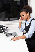 Young businesswoman using cell phone in front of laptop at desk in office