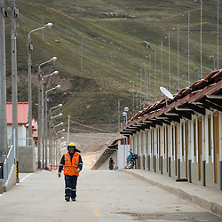 A worker walks past a row of newly constructed houses in Carhuacoto, a town built by Chinese mining company Chinalco to relocate the residents of Morococha in the central Peruvian Andes.