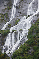 Ribbon-like waterfall in the Tongass National Forest carrying fresh water to the salt water of the Endicott Arm fjord of Tracy Arm - Fords Terror Wilderness.  Southeast.  Inside Passage.  Summer.  Afternoon.