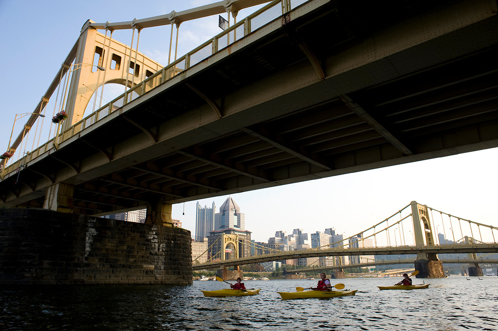 Kayakers paddle past the 9th Street Bridge on the Allegheny River in Pittsburgh while participating in Venture Outdoors' Fireworks Paddle.