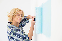 Beautiful woman painting wall with paint roller