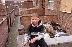 Young boy sitting on brick wall in back alley of housing estate with piles of rubbish in yard; Forest Fields Nottingham,