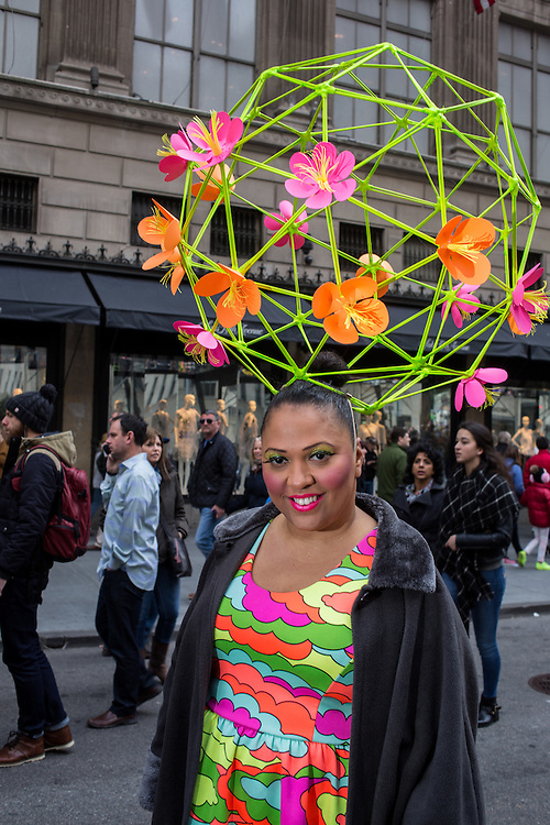 New York, NY, USA-27 March 2016. A woman wearing  a hat like a geodesic done with flowers on Fifth Avenue in the annual Easter Bonnet Parade and Festival.