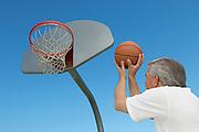 Senior man aiming basketball at hoop, outdoors