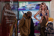 A man walks two Muslim women and an image of a girl wearing a bikini in a high-street advert for sunbeds, on 26th December 2016, in Bristol's Broadmead, England UK.