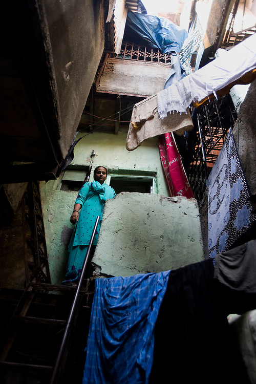 """Akthari Sheik 42 years old, climbs out of her house in Razzaq chawl at the Behrampada area, in Mumbai, India, on Tuesday February 11, 2009. She was a typical Muslim girl who was bought up in the closed walls of her family home and later at her husbands house. She did not have confidence to speak to anyone, including her peers. She said she used to cry while even speaking. The there were troubles in the marraige. Her husband married 3 other women, this she could not bear. So she fought at home, and left home to take care of her own life and earn and make a living for herself.She wrote exams got herself educated attended WRAg sessions and became self sufficient.Her family was initially very sarcastic and critical of her going to college. But she says """"I could actually see a college, we used to go out roaming after college, attend programmes and she felt like she was having a life."""".She learnt Phenyl making, painting, tailoring, embroidery and other such skills of sustainance..She has the confidence today to face the society..Single women were not admitted to function, marriage ceremonies etc, but nor WRAG member invite all the widow and single women and give them a place in society..Photographer: Prashanth Vishwanathan"""