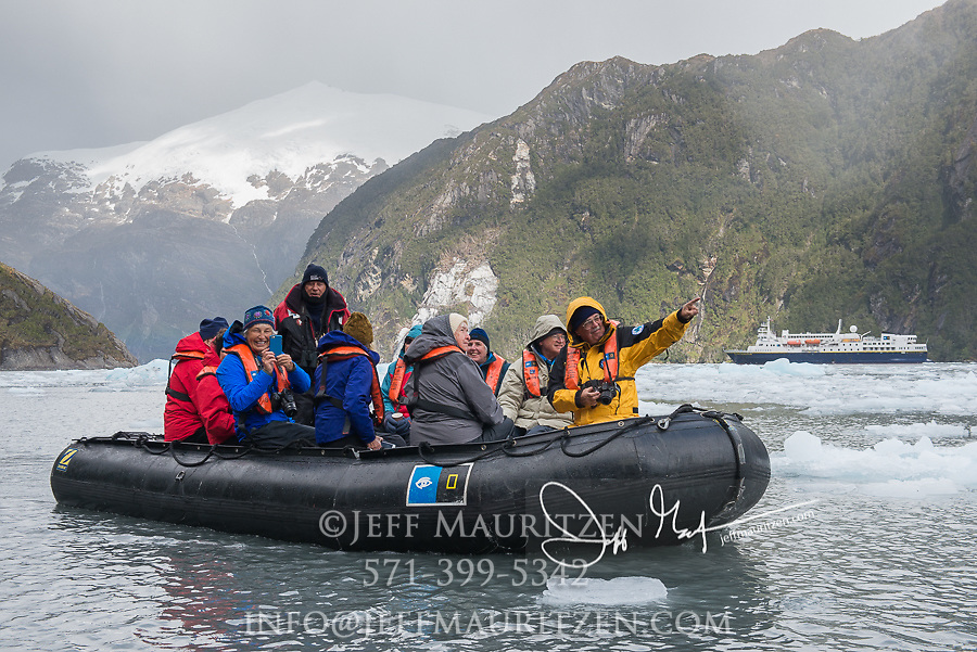 Expedition travelers aboard zodiac inflatable boats explore Garibaldi glacier national park in Parque Nacional Alberto de Agostini, Chile.