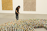 "A woman takes a photograph of an installation of thousands of beer cans entitled ""Halam Tawaal"", by Kader Atlia, in the Lehmann Maupin booth."