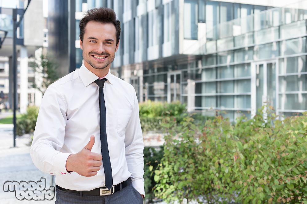 Portrait of happy businessman showing thumbs up outside office building