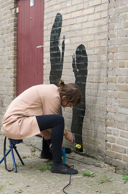 Nederland, Den Bosch, 20120921..Kunstenaarsproject De Verwonderstraat in Den Bosch..Kunstenares Jitske Blom plakt silhouetten op de achterkant van huizen in de wijk Orthen..De silhouetten zijn van buurtbewoners. .Buurt project in de wijk Orthen...Netherlands, Den Bosch, 20120921. Artists Project Marvel Street in Den Bosch. Artist Jitske Blom sticks silhouettes on the back of houses in the district Orthen. The silhouettes are of residents. ?Neighbourhood project in the district Orthen.