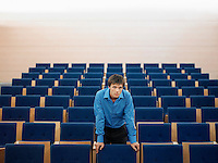 Businessman standing alone leaning on chair in Auditorium portrait