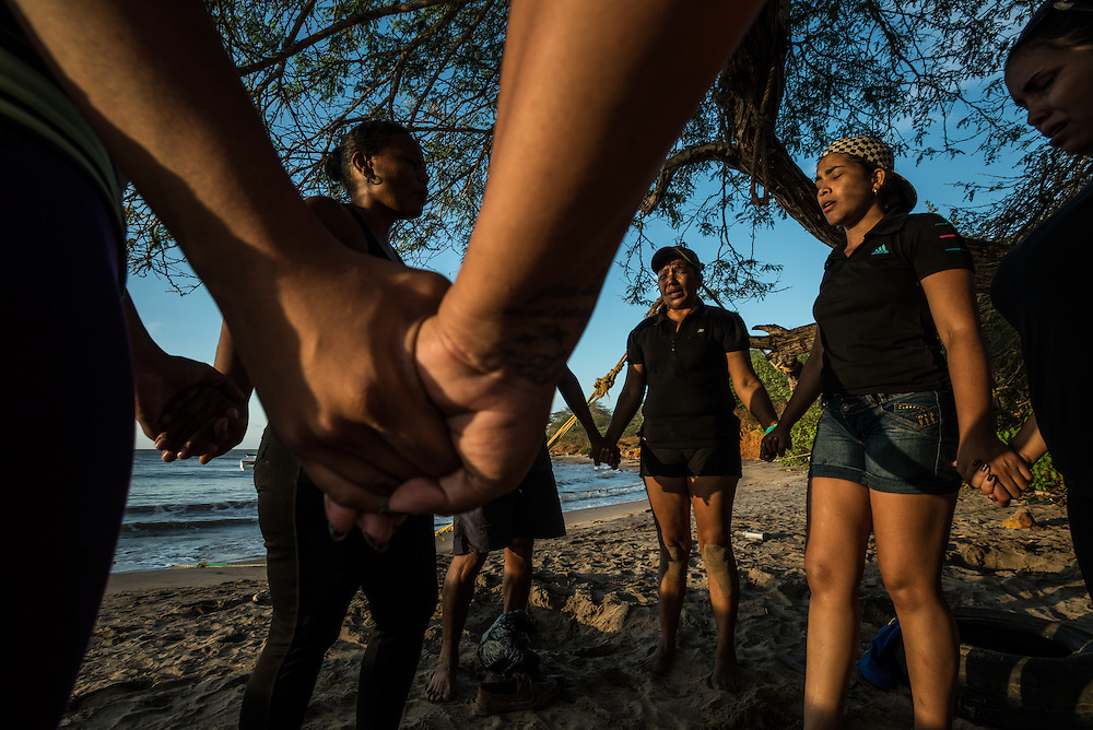 FALCÓN, VENEZUELA - SEPTEMBER 26, 2016: Maria Piñero and other undocumented migrants joined hands and prayed together on the beach for safety during their difficult and risky journey, just before boarding the smuggler's boat that will illegally take them from Venezuela to Curaçao.  Ms. Piñero was very afraid, but was determined to make the trip and make a better life for herself and her family in Curacao.  Undocumented migrants here have mortgaged property, sold kitchen appliances and even borrowed money from the same smuggling rings that pack them on the floorboards alongside drugs and other contraband. The journey to Curaçao takes them on a 60-mile crossing filled with backbreaking swells, gangs of armed boatmen and coast guard vessels looking to capture migrants and send them home. Then, after being tossed overboard and left to swim ashore, they hide in the brush to meet contacts who spirit them anew into the tourist economy of this Caribbean island. They clean the floors of restaurants, work in construction, sell trinkets on the street, or even solicit Dutch tourists for sex. But at least, the migrants say, there is food. PHOTO: Meridith Kohut for The New York Times