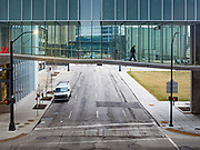 """24 MARCH 2020 - DES MOINES, IOWA: A solitary person walks through the Des Moines skywalk. The city was deserted Tuesday as most people chose to work from home or stay in their homes. On Tuesday morning, 24 March, Iowa reported over 120 confirmed cases of the Coronavirus (SARS-CoV-2) and COVID-19. Restaurants, bars, movie theaters, places that draw crowds are closed for at least 30 days. The Governor has not ordered """"shelter in place""""  but several Mayors, including the Mayor of Des Moines, have asked residents to stay in their homes for all but the essential needs. People are being encouraged to practice """"social distancing"""" and many businesses are requiring or encouraging employees to telecommute.        PHOTO BY JACK KURTZ"""