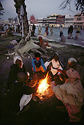 Pilgrims warm themselves in the predawn chill on the bank of the Ganges. Every 12 years, millions of devout Hindus celebrate the month-long festival of Kumbh Mela by bathing in the holy waters of the Ganges at Hardiwar, India. Hundreds of ashrams set up dusty, sprawling camps that stretch for miles. Under the watchful eye of police and lifeguards, the faithful throng to bathe in the river.