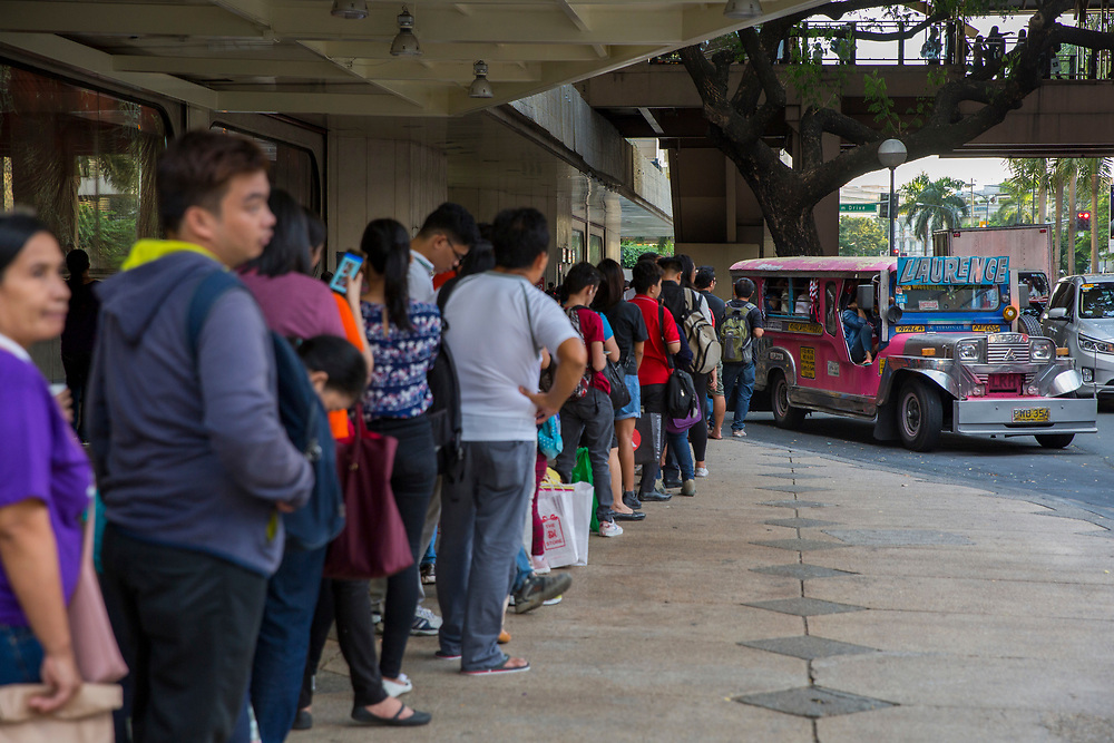 People queueing up to board the local free Jeepney in Makati, Metro Manila, Philippines. A Jeepneys, or 'Dyipni' in Filipino, are repurposed US military jeeps left over from WWII that have become a prevalent symbol of Philippine art and culture.  (photo by Andrew Aitchison / In pictures via Getty Images)