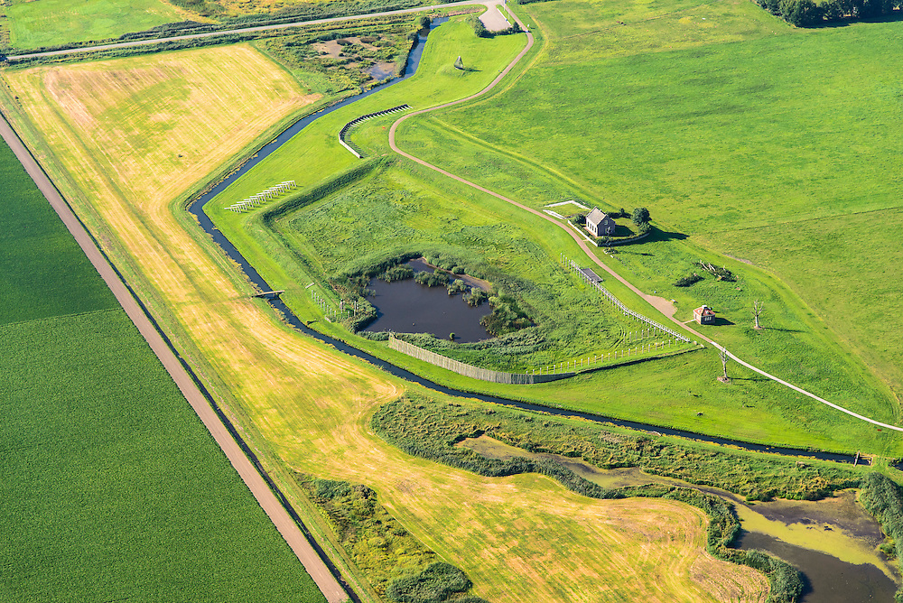 Nederland, Noordoostpolder, Schokland, 27-08-2013. Dorp en voormalig eiland in de Zuiderzee. Voormalige haven en vuurtoren, lichtwachterswoning. Onderdeel van de UNESCO Werelderfgoedlijst. <br /> Het verlagen van de grondwaterspiegel in de Noordoostpolder leidt tot inklinking waardoor het eiland steeds lager komt te liggen. Om verder wegzinken te voorkomen een hydrologische zone aangelegd<br /> Village and former island, former harbor and lighthouse, light house keeper residence. Part of the UNESCO World Heritage List. Lowering the groundwater level in the Noordoostpolder leads to subsidence and causes the island the sink away. In order to prevent further decline a hydrological zone has been created.<br /> luchtfoto (toeslag op standaard tarieven);<br /> aerial photo (additional fee required);<br /> copyright foto/photo Siebe Swart.