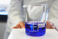 Scientific glass container with blue liquid technician in background