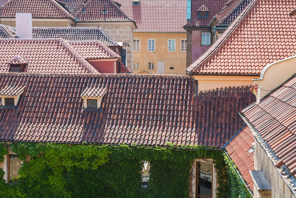 Clay roofing tiles on random rooftops in Prague form patterns