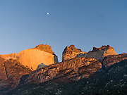A golden sunrise illuminates the Horns, seen from Albergue Los Cuernos, a refuge (hut) in Torres del Paine National Park, Chile, Patagonia, South America. The moon sets in a blue sky.
