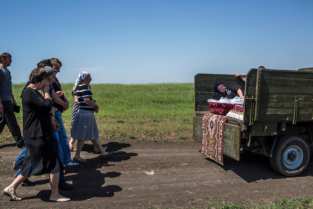 Mourners process with the casket of Elena Ott, 42, from her family's house to a local cemetery on May 16, 2014 in Starovarvarovka, Ukraine. Ott was killed two days prior when the car she was riding in was fired on by forces her family believes to be the Ukrainian military.