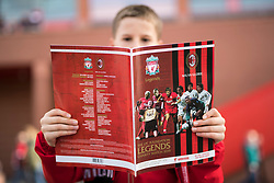 LIVERPOOL, ENGLAND - Saturday, March 23, 2019: A young supporter reads the match-day programme outside Anfield before the LFC Foundation charity match between Liverpool FC Legends and Milan Glorie at Anfield. (Pic by Paul Greenwood/Propaganda)