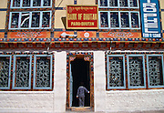 Small child standing in the doorway of the bank in Paro, Bhutan