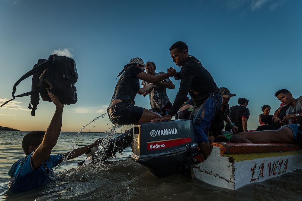 FALCÓN, VENEZUELA - SEPTEMBER 26, 2016: Undocumented migrants board a smuggler's boat that will illegally take them from Venezuela to Curaçao. Undocumented migrants here have mortgaged property, sold kitchen appliances and even borrowed money from the same smuggling rings that pack them on the floorboards alongside drugs and other contraband. The journey to Curaçao takes them on a 60-mile crossing filled with backbreaking swells, gangs of armed boatmen and coast guard vessels looking to capture migrants and send them home. Then, after being tossed overboard and left to swim ashore, they hide in the brush to meet contacts who spirit them anew into the tourist economy of this Caribbean island. They clean the floors of restaurants, work in construction, sell trinkets on the street, or even solicit Dutch tourists for sex. But at least, the migrants say, there is food. PHOTO: Meridith Kohut for The New York Times