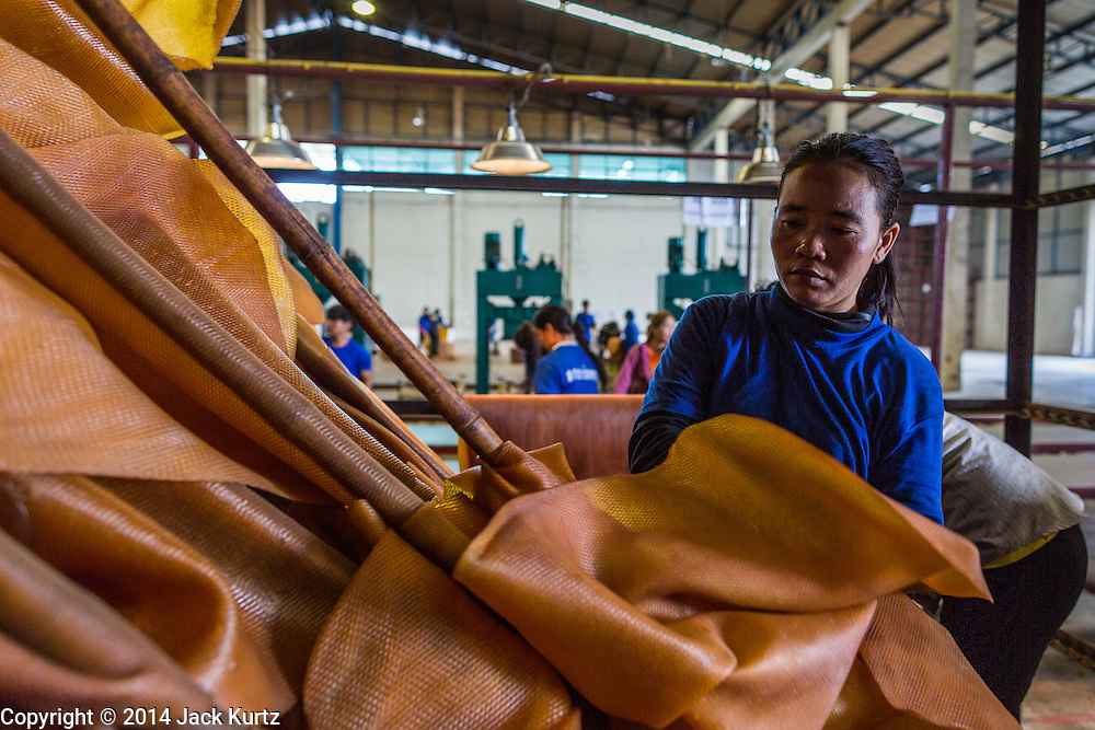 02 SEPTEMBER 2014 - BO THONG, CHONBURI, THAILAND: A worker at Bothong Rubber Fund Cooperative in Bo Thong, Chonburi, Thailand, pulls rubber sheets off hangers after they were dried in a large smoker. Thailand is the leading rubber exporter in the world. In the last two years, the price paid to rubber farmers has plunged from approximately 190 Baht per kilo (about $6.10 US) to 52 Baht per kilo (about $1.60 US). It costs about 65 Baht per kilo to produce rubber ($2.05 US). A rubber farmer in southern Thailand committed suicide over the weekend, allegedly because the low prices meant he couldn't provide for his family. Other rubber farmers have taken jobs in the construction trade or in Bangkok to provide for their families during the slump.    PHOTO BY JACK KURTZ