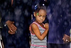 Samariah Johnson, 6, watches from under a tent as rain falls during funeral services for Cynthia Hurd, librarian and community leader, Saturday, June 27, 2015 at Emanuel AME Church. Paul Zoeller/Staff