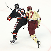Torin Snyderman #17 of the Northeastern Huskies and Destry Straight #17 of the Boston College Eagles fight for the puck during The Beanpot Championship Game at TD Garden on February 10, 2014 in Boston, Massachusetts. (Photo by Elan Kawesch)