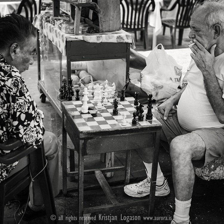 Older men smoking while playing chess at a central square in Veracruz Mexico