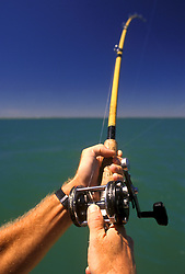 Stock photo of a man holding a bending rod fishing in the Gulf of Mexico