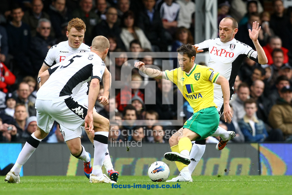 Picture by Paul Chesterton/Focus Images Ltd.  07904 640267.31/03/12.Wes Hoolahan of Norwich is surrounded by John Arne Riise of Fulham, Brede Hangeland of Fulham and Danny Murphy of Fulham during the Barclays Premier League match at Craven Cottage stadium, London.