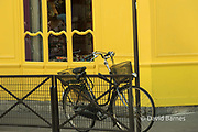 France, Paris (75), Bicycle locked to a rail outside the wind of a yellow building