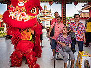 28 JANUARY 2017 - SAMUT PRAKAN, SAMUT PRAKAN, THAILAND: A Thai-Chinese family watch a lion dance before the Chinese New Year Lantern Festival at the Tham Katanyu Foundation shrine in Samut Prakan, a suburb about 15 miles from Bangkok. More than 5,000 handmade lanterns imported from Taiwan are hung on the grounds of the shrine. Some of the lanterns are traditional Chinese lanterns, others are in the shapes of people or deities. There is also traditional Chinese entertainment, likes lion dances, at the festival.     PHOTO BY JACK KURTZ