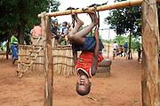 Mozambique, Afrique, Africa,  ACDI.Mozambique, sud-est de l'Afrique. Dans une cour d'e?cole primaire, ce petit garc?on qui e?tait d'une grande agilite? s'amusait a? se suspendre la te?te en bas.