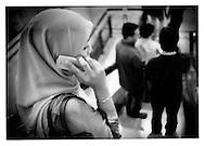 Young Malay woman, wearing hijab (tudong, in Malay) , talks on mobile telephone while descending escalator in KLCC shopping mall, Kuala Lumpur, Malaysia.