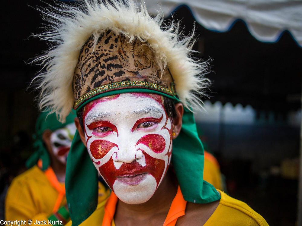 06 FEBRUARY 2014 - HAT YAI, SONGKHLA, THAILAND: A member of a traditional folk dance troupe waits to perform for Lunar New Year at the Chinese New Year Festival at the Tong Sia Siang Tueng Shrine in Hat Yai. Hat Yai was originally settled by Chinese immigrants and still has a large ethnic Chinese population. Chinese holidays, especially Lunar New Year (Tet) and the Vegetarian Festival are important citywide holidays.     PHOTO BY JACK KURTZ