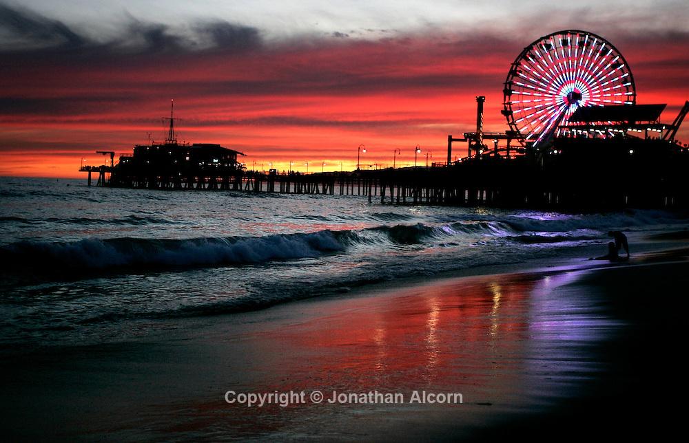 Aug. 03, 2009 - Santa Monica, California, U.S. - A lone skim board tries to catch the shore break at sunset at the Santa Monica Pier and the Pacific Park.
