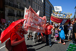 © Licensed to London News Pictures. 30/06/2018. London, UK. People stand around a giant 70th anniversary cake as thousands of people take part in a march through central London to mark the 70th anniversary of the NHS. The UK's National Health Service was launched on July 5th, 1948 as part of major social reforms following the Second World War. Photo credit: Ben Cawthra/LNP