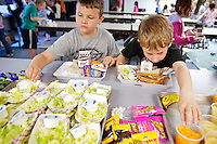 Calvin Longbrake reaches for a cup of oranges as his first-grade classmate Gage Davenport selects a salad for lunch Friday at Mullan Trail Elementary in Post Falls. Mullan Trail was one of 116 Idaho schools awarded grants this year to provide students with a variety of free fresh fruits and vegetables.
