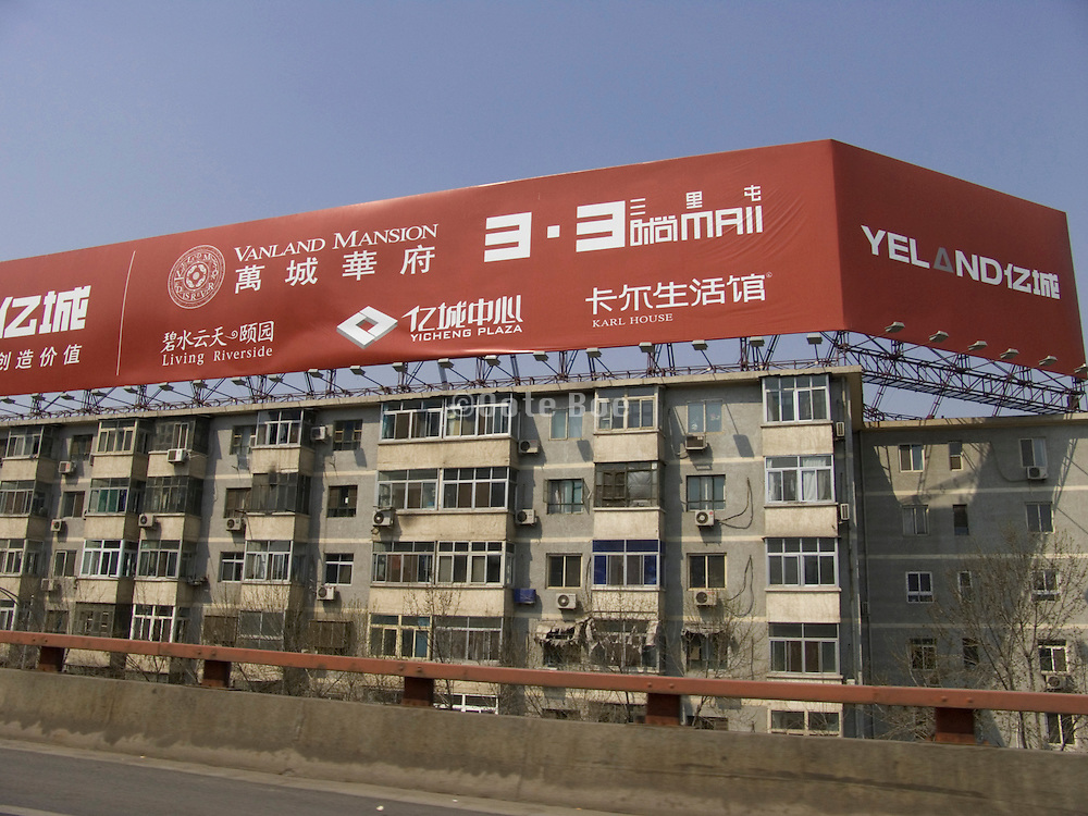 old residential building with big billboard advertisement for new luxurious man'sions Beijing China
